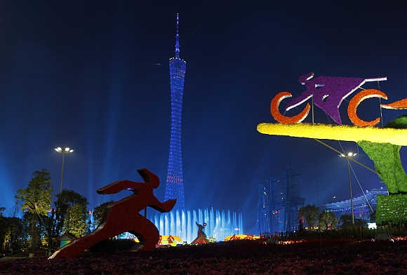Sports sculptures are pictured in front of the Canton TV Tower, also known as Guangzhou TV Tower, lit by coloured lights in Guangzhou, in Guangdong province, China.