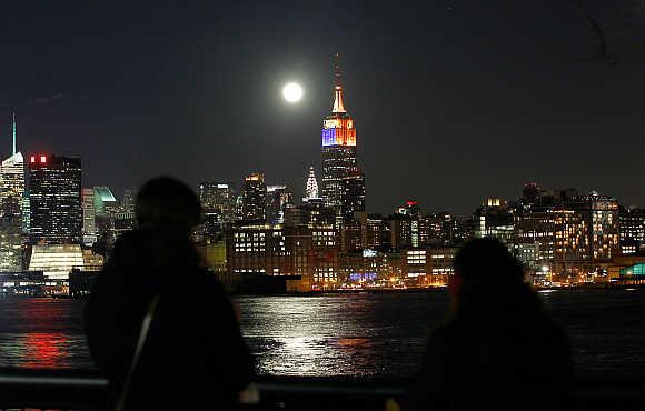 A full moon rises behind the Empire State Building and the skyline of New York as people watch from a park along the Hudson River in Hoboken, New Jersey.
