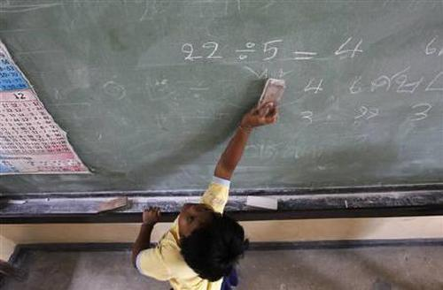 A student cleans a blackboard at a school.