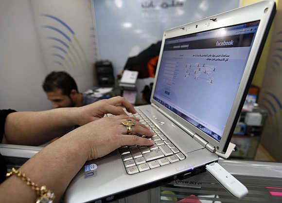 A woman uses wireless Internet at a shop in Baghdad, Iraq.