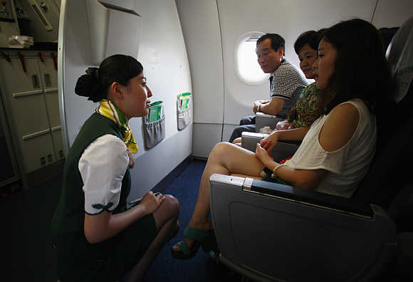 A crew member of Spring Airlines talks with travellers onboard an Airbus A320 aircraft at Hongqiao airport in Shanghai.