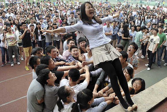 A teacher falls backwards from a higher ground as students get ready to catch her during a pressure releasing exercise ahead of the National College Entrance Exams at a high school in Chongqing municipality.
