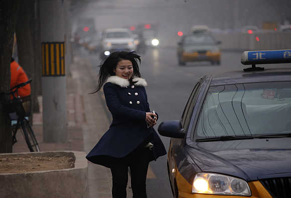 A woman smiles as she runs to a taxi on a hazy day of Beijing.