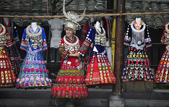 A visitor tries on a Miao ethnic gown in Leishan county, southeast Guizhou province.