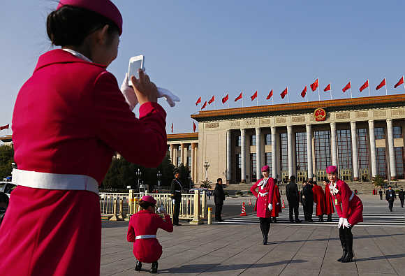 Hotel guides pose for a photo in front of the Great Hall of the People in Beijing.