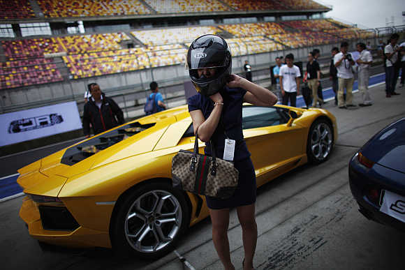 A woman puts on a helmet as she stands next to a Lamborghini in Shanghai.