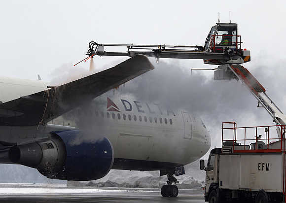 An employee de-ices the wing of a Delta plane at Munich's international airport early in Germany.