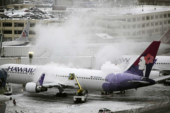 A Hawaiian Airlines plane undergoes de-icing before takeoff at Seattle-Tacoma International Airport in Seatac, Washington, United States.