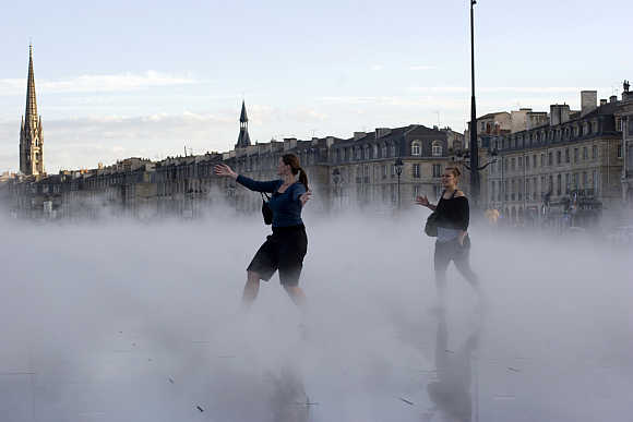 Tourists walk through artificial fog at the Miroir d'Eau (Mirror of Water), a public art piece on the quay of the Garonne River in Bordeaux.