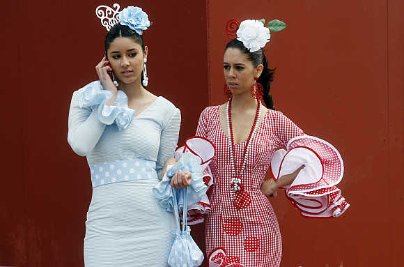 Women wearing Sevillana dresses take part in the April fair in Seville.
