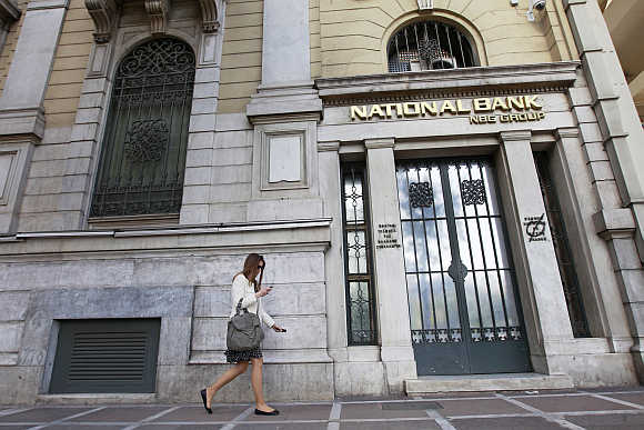 A woman walks outside a National Bank of Greece branch in central Athens.