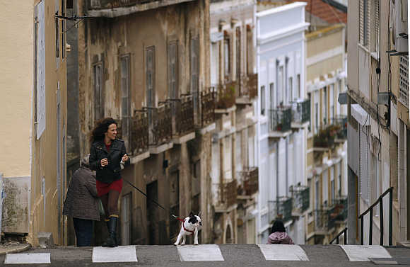 A woman walks her dog in Lisbon.