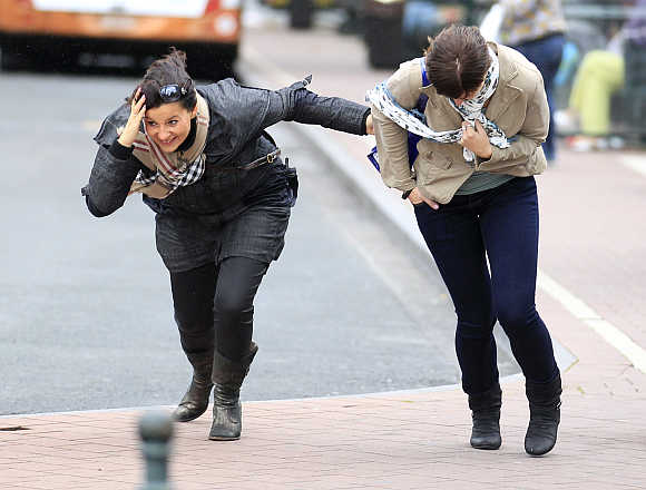 Women help each other to cross a square during strong wind in central Brussels.