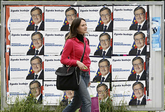 A woman passes posters of a politician in the centre of Warsaw.