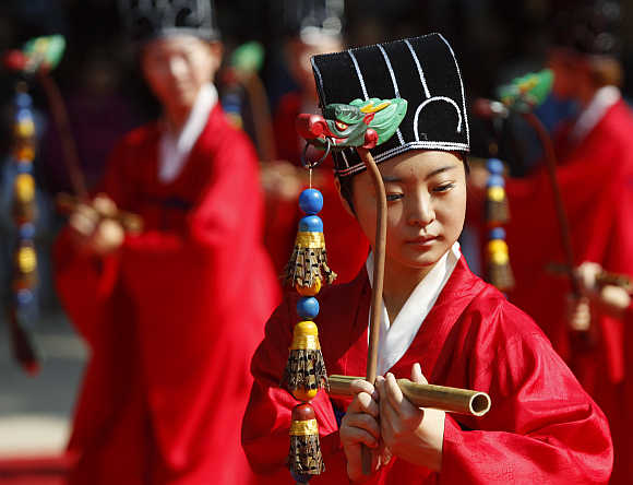 A university student wears traditional costume while peforming during the grand Confucian ceremony at Sungkyunkwan University in Seoul.