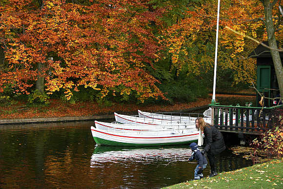 A mother and her child play near the water in front of boats and autumn trees in Frederiksberg Garden in Copenhagen.