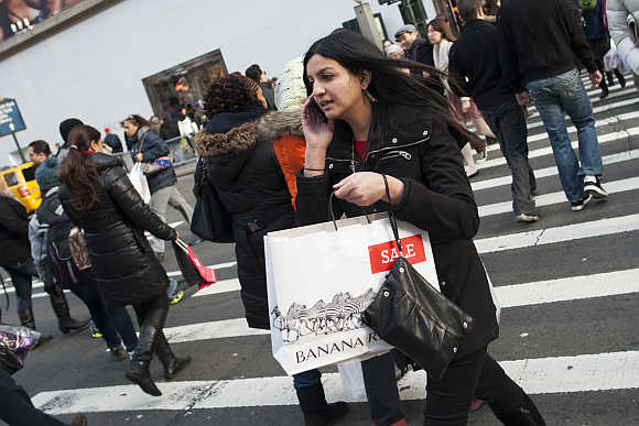 People carry shopping bags as they make their way in Herald Square in New York City.