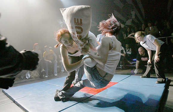 Amateurs prepare for Pillow Fight League as referee Sarah Bellum, right, watches during a late night event in Toronto.