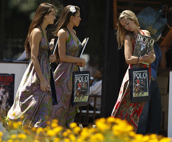 Women walk with polo magazines at the Campo Argentino de Polo in the Buenos Aires.