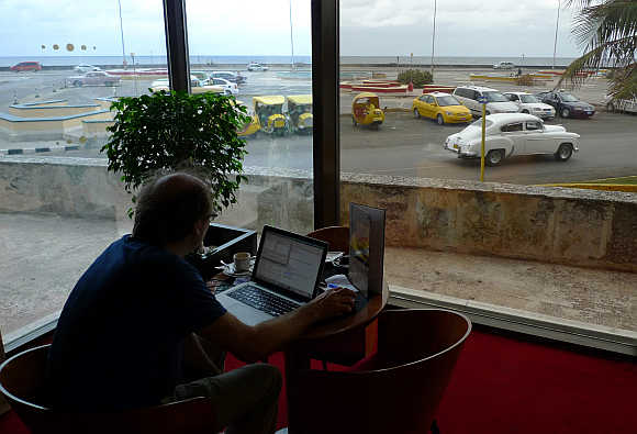 A man surfs the Internet using a wireless connection in the lobby of a hotel in Havana, Cuba.
