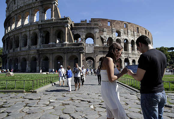 Tourists use an iPad tablet in front of Rome's ancient Colosseum, Italy.