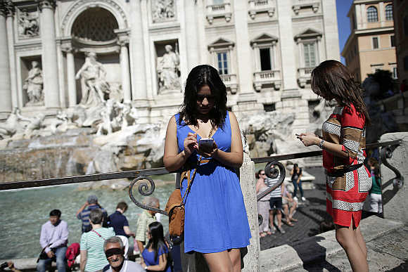 Women use smartphones in front of the Trevi Fountain in Rome, Italy.