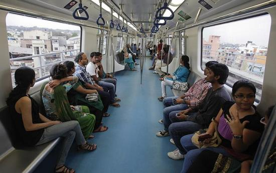 Commuters ride inside a carriage of a Namma Metro as it travels along an elevated track in the Indira Nagar area of Bangalore.