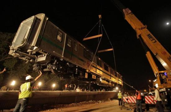 A Metro rail carriage is lifted on to a track.