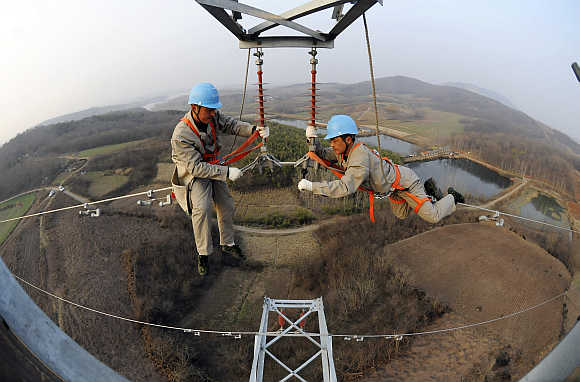 Workers check on electricity pylon situated amid farmlands in Chuzhou, Anhui province, China.