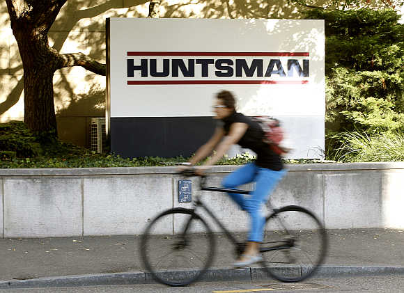 A woman cycles past the logo of US chemical company Huntsman in front of a plant in Basel, Switzerland.