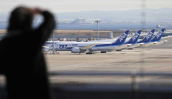 A woman looks at All Nippon Airways' Boeing's 787 Dreamliner planes at Haneda airport in Tokyo, Japan.