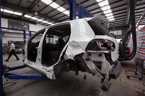 A crashed car is under repaired at a service centre.