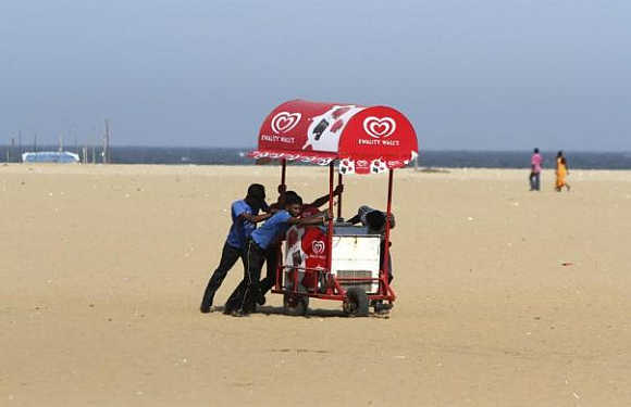 Workers move an ice-cream cart from the Marina beach in Chennai.
