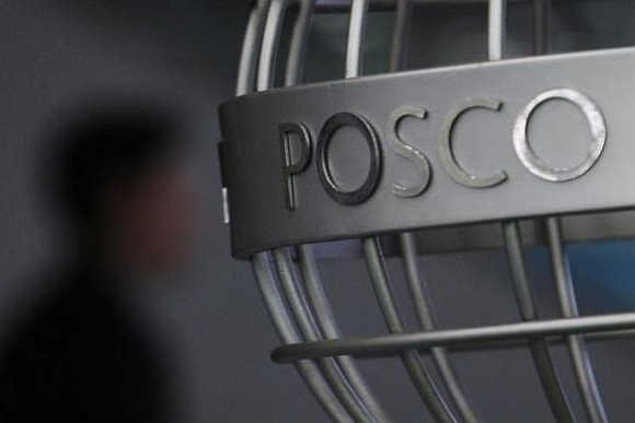 A man walks past a Posco logo at the company's headquarters in Seoul, South Korea.