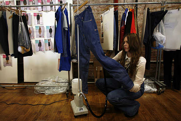 A woman steams a pair of jeans backstage during a fashion show New York.
