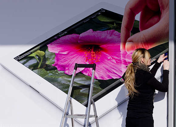 A woman pastes an advertising poster showing Apple's iPad tablet computer to the window of an electronic retailer in Berlin, Germany.