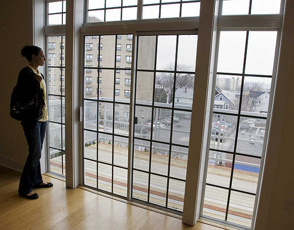 Prospective home buyer Jessica Doctoroff looks out the windows of a condominium for sale in Somerville, Massachusetts.