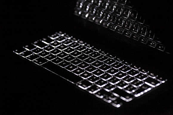 Backlit keyboard is reflected in screen of Apple Macbook Pro notebook computer in Warsaw, Poland.
