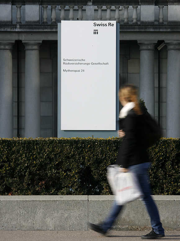 A woman walks past the headquarters of Swiss reinsurer Swiss Re in Zurich.