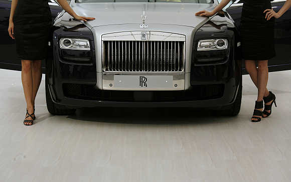 Models pose beside a Rolls Royce Ghost in Hong Kong.