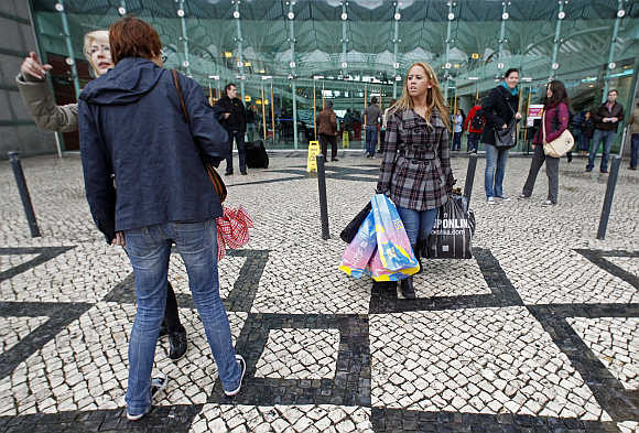 People walk outside the entrance of a shopping mall in Lisbon.