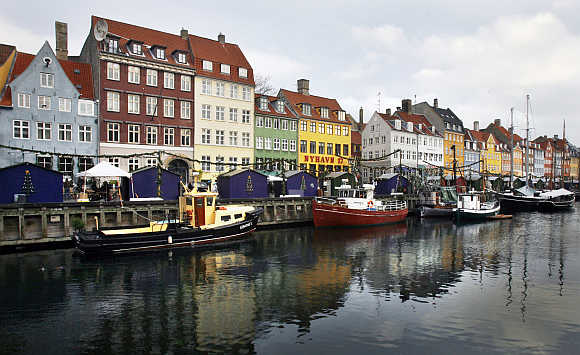 Boats are anchored at the 17th century Nyhavn district, home to many shops and restaurants in Copenhagen.