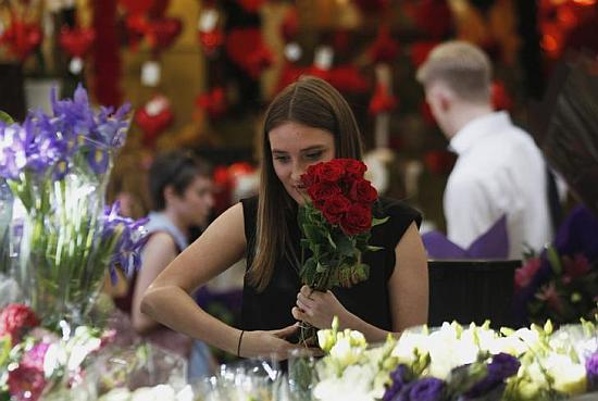 A worker prepares a red roses bouquet to be sold as a Valentine's Day special.