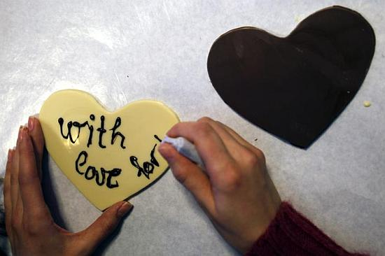 A woman writes a love message on a small chocolate heart.