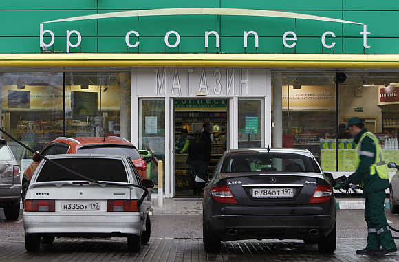 A pump attendant fills cars at a petrol station in Moscow.