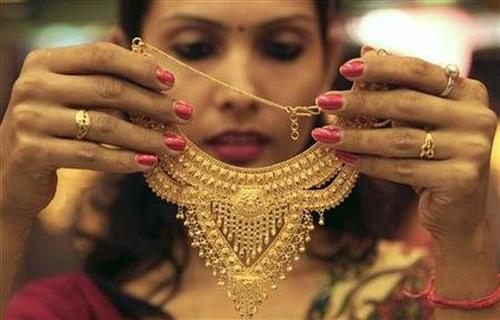 A salesgirl shows a gold necklace to customers at a jewellery showroom in Chandigarh.