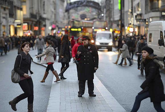 Pedestrians walk along Oxford Street in London.