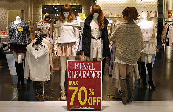 A woman works next to a sale sign at a shopping district in Tokyo.