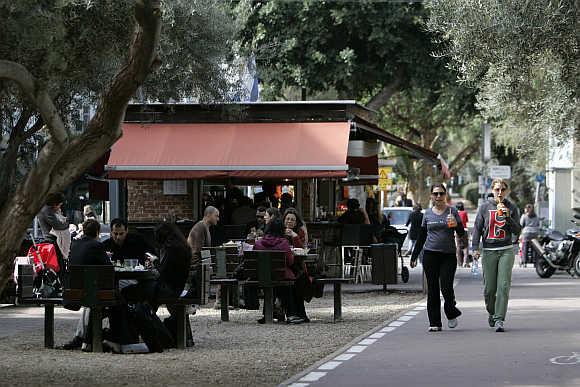 People walk past a cafe in Tel Aviv.