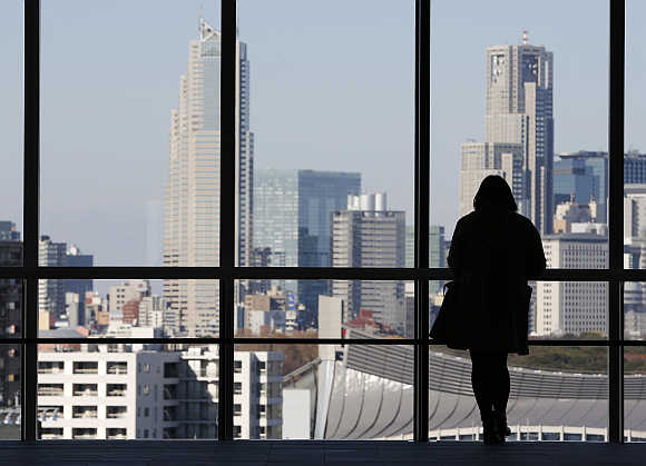 A woman looks at highrise buildings in Tokyo, Japan.